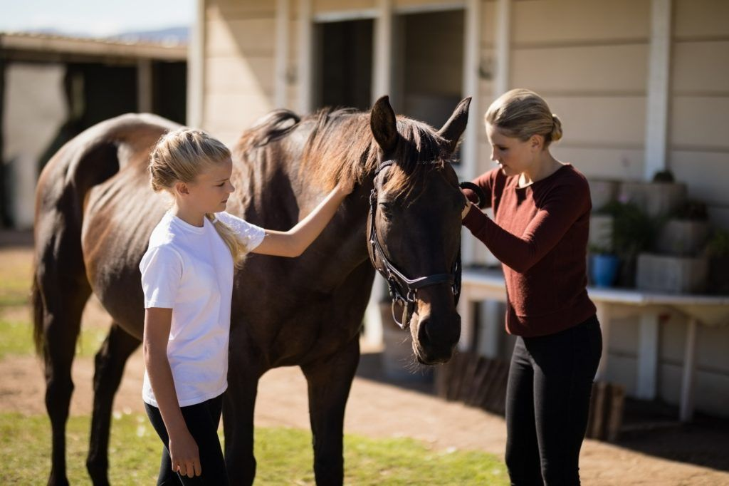 Mother and daughter touching the horse